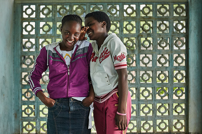 Two girls laugh at school in Zimbabwe