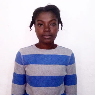 Angelina,17, is looking into the camera and is wearing a striped top