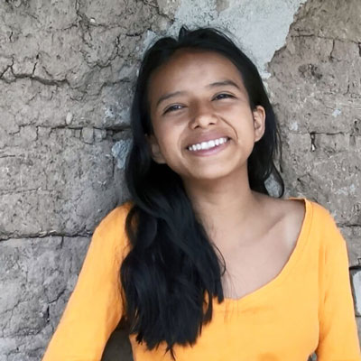 María-Alicia, 11, is smiling and wearing a yellow-orange top