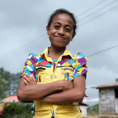 Santina, 8 is smiling and folding her arms
