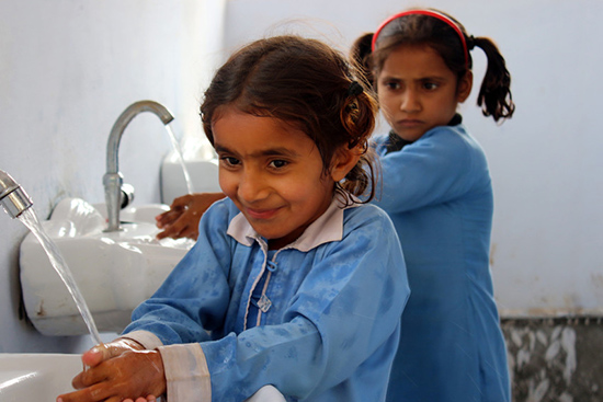 Two young girls in school uniforms wash their hands in basins with taps
