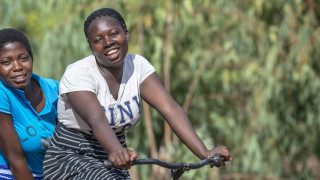 Two adolescent girls on a bike in Malawi