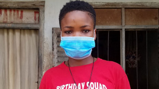 Sonia from Cameroon stands outside her home wearing a face mask