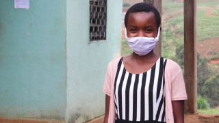 12 year old Sirri from Cameroon is wearing a mask and smiling to the camera