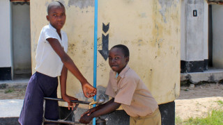 Boys washing their hands using a new water tank, in Zimbabwe