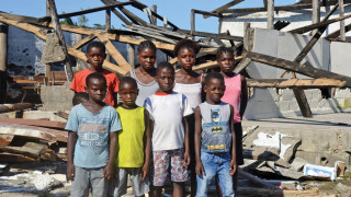 Children stand in the ruins of their school destroyed by cyclone Idai