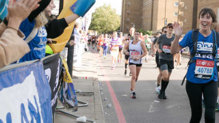 Runner for Plan International UK waving at staff cheering along the route