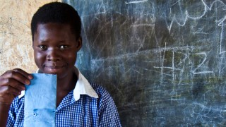 A girl holds a sanitary pad made from locally sourced materials in Uganda.
