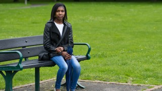 Dannetta sits on a bench in the park