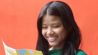 A girl reads a birthday card
