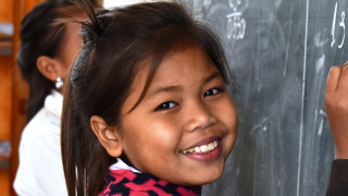 Thueam, 11, writes on the blackboard in her new classroom in Laos