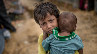 Sameera, 7, holds her brother Omar, who is 7 months old, in front of their temporary shelter in a camp in Cox's Bazar, Bangladesh. Both are suffering from cold and fever. Photo: Turjoy Chowdhury/Disasters Emergency Committee