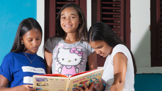 Girls read a book together in the Dominican Republic
