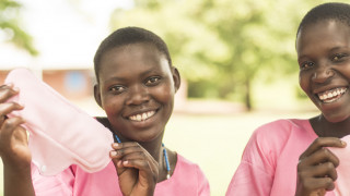 Two girls hold up reusable sanitary pads