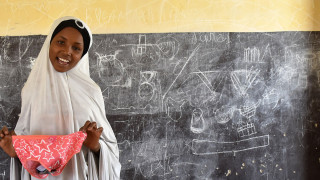 Photo of a girl with items from her sanitary pad kit