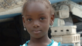 Girl stands by her destroyed home after Haiti earthquake