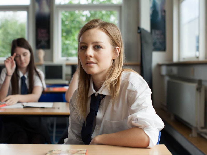 Girl sitting at a desk in a UK classroom