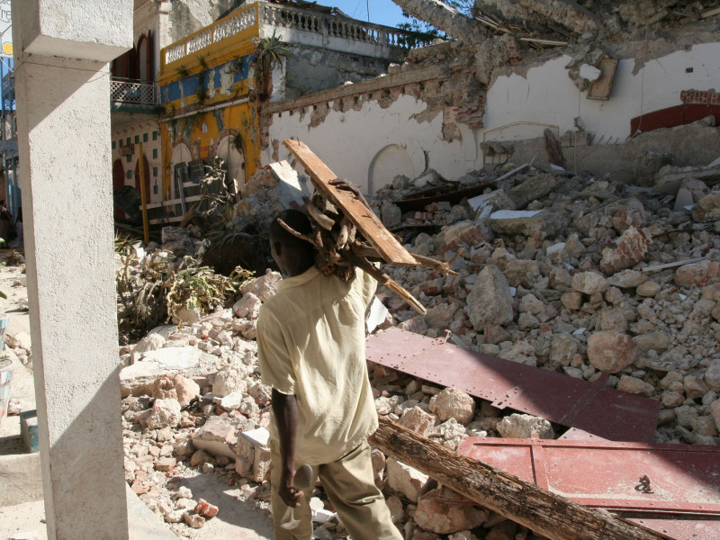 A man walks past destroyed homes in Haiti