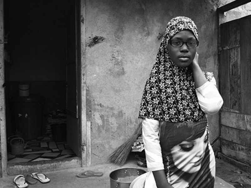 Ghana-Rose stands in front of her home