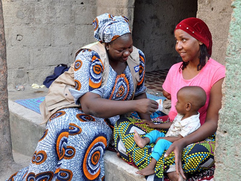 Photo of a health worker treating a baby for malnutrition