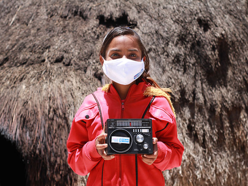 Photo of a girl in a face mask holding a radio