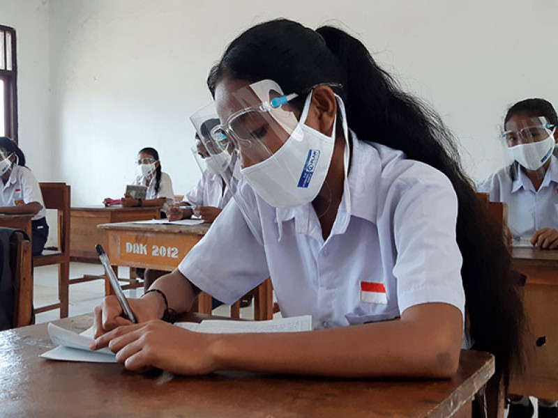 A girl wears a mask and face shield in a classroom