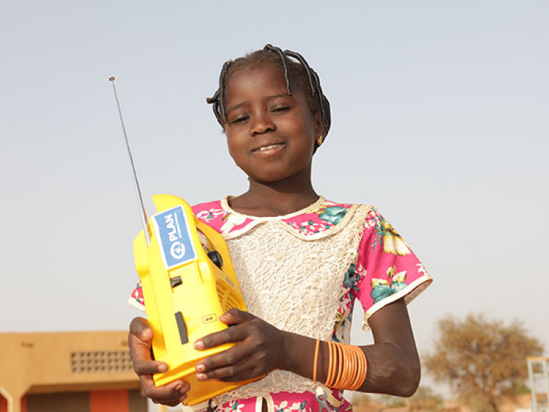 Photo of a girl holding a yellow radio