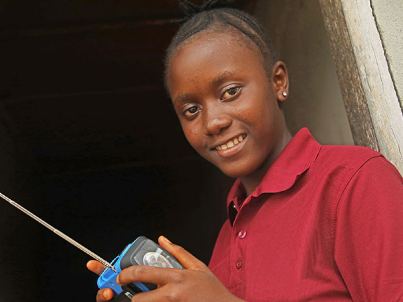 Photo of a girl in a red top holding a radio