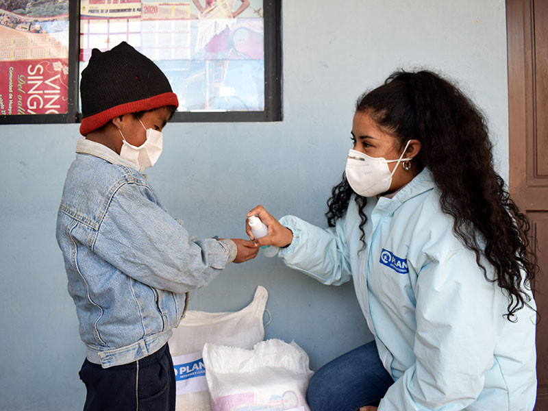 Photo of a boy receiving hand sanitiser