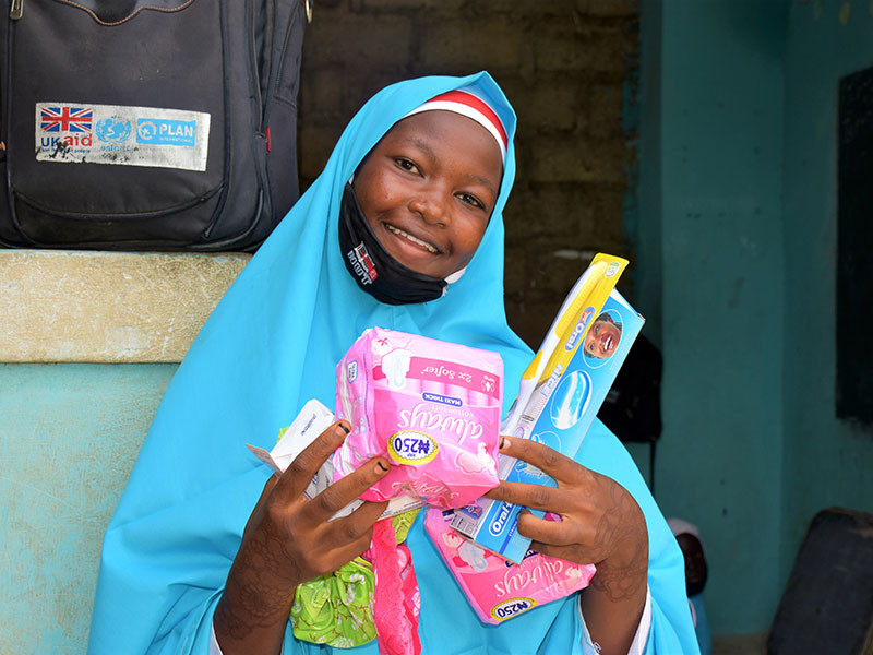 Photo of a girl holding items from a hygiene kit