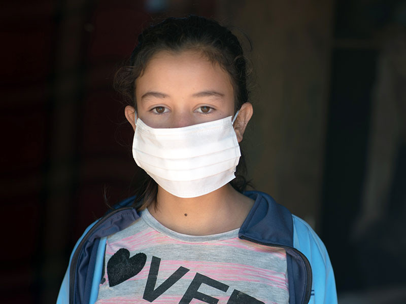 Photo of a girl wearing a white face mask
