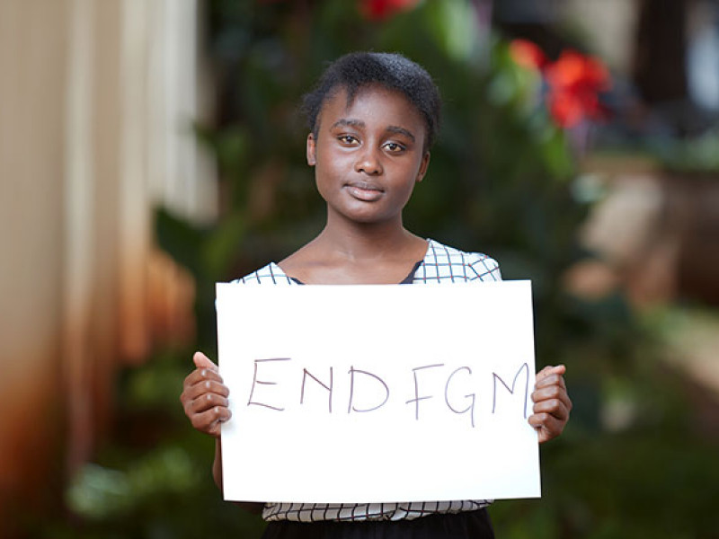A girl holds a sign calling for an end to FGM