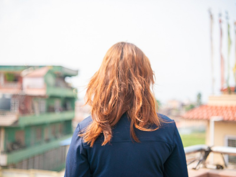 A girls looks out over a balcony