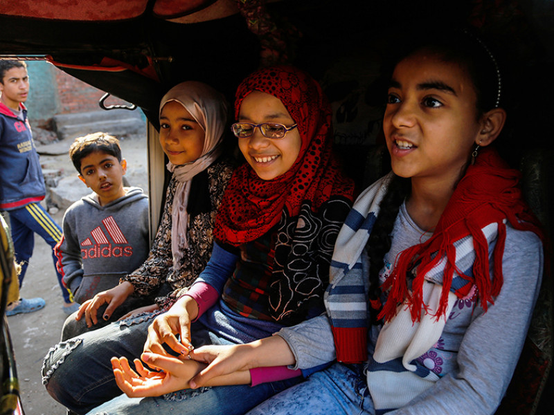 Nada travels in a tuk-tuk with her friends in Cairo