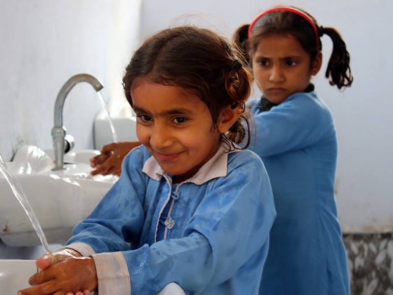 Amna washes her hands with soap in Pakistan
