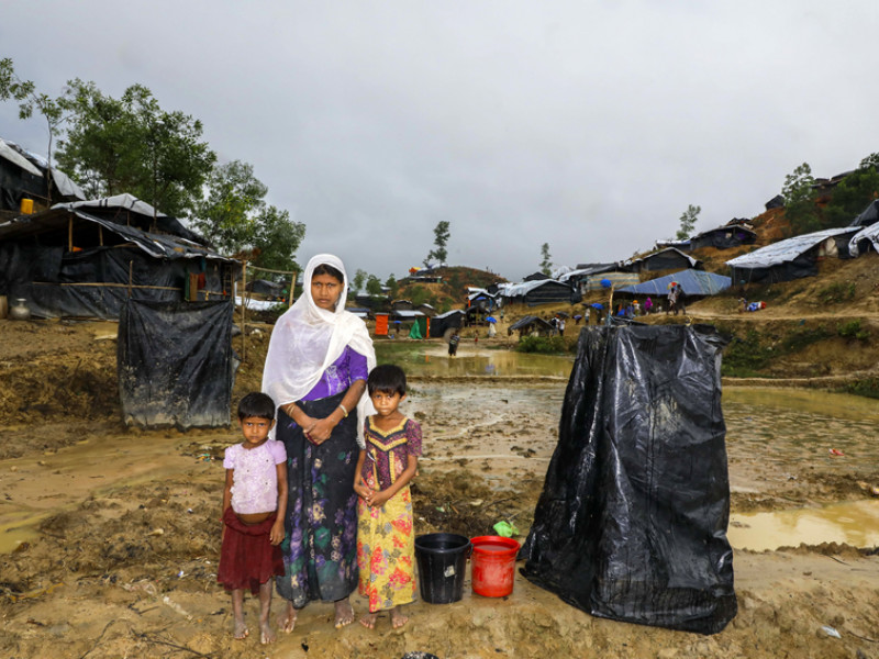 Modina and her two daughters next to a makeshift toilet in their camp in Cox's Bazar, Bangladesh