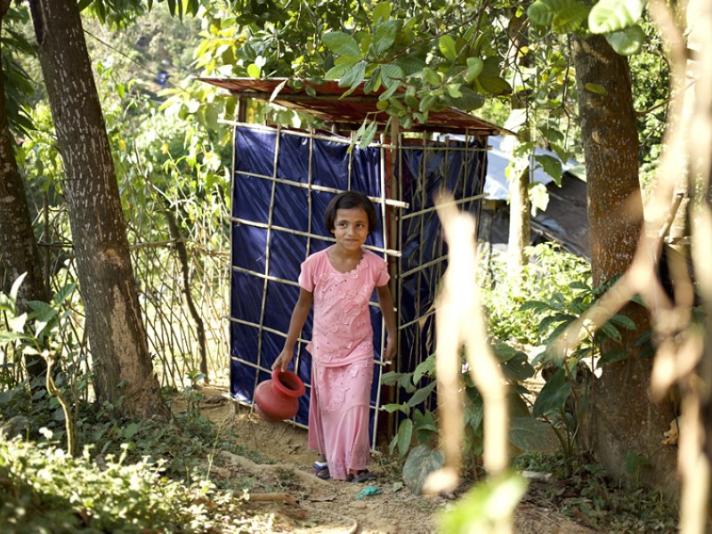 A girl uses one of the toilets built by Plan International in one of the camps in Cox's Bazar