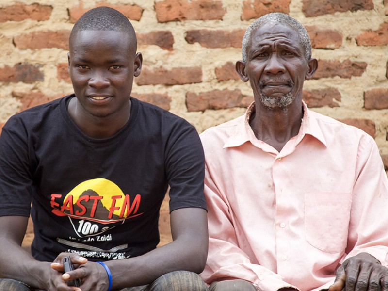 Allan and his father Nkono at home in Uganda