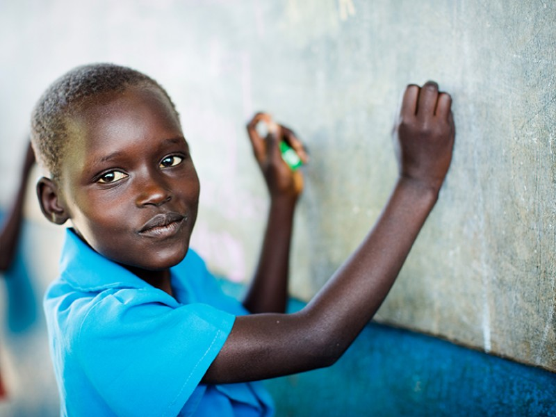 A girls writes on a blackboard at an Early Childhood Care and Development Centre in Uganda.