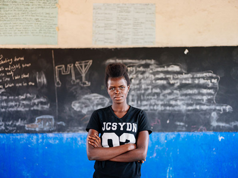 A girl stands in front of a blackboard