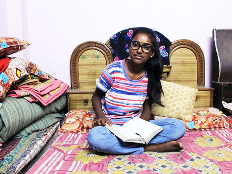A girl sits on a bed with a book on her lap