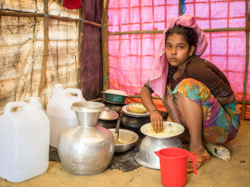 A girl prepares a meal in her tent, Bangladesh