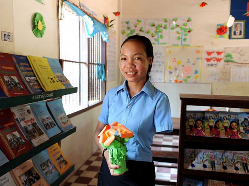 A girl stands in front of some books in Cambodia