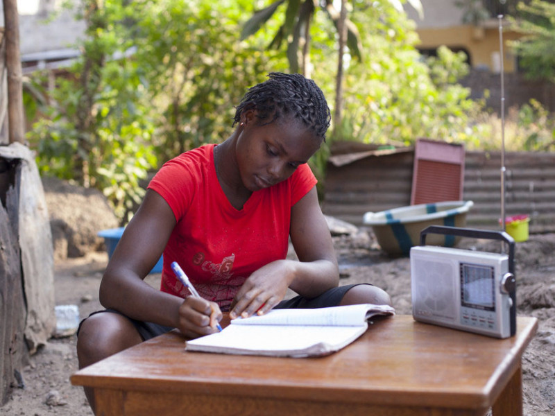 A girl writes in a book in Sierra Leone