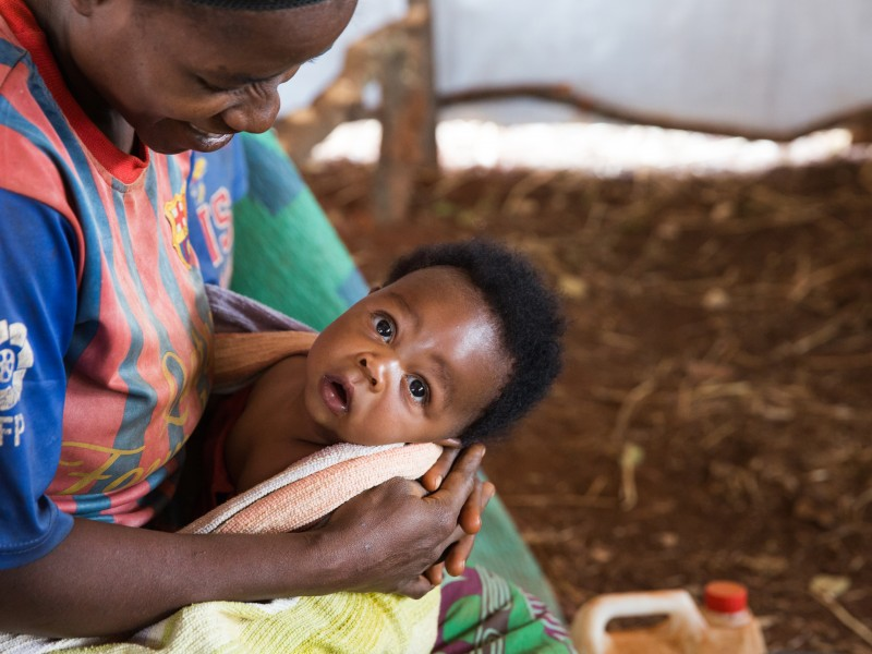 Burundi refugee mum smiles at her baby