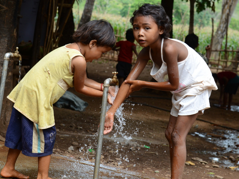 Children collect water from a water point installed by Plan International