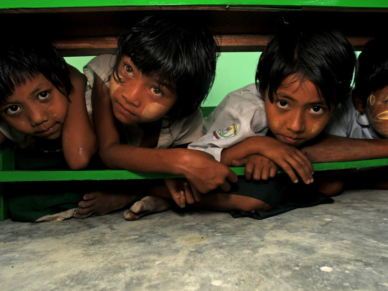 Children hide under tables after a disaster drill rings