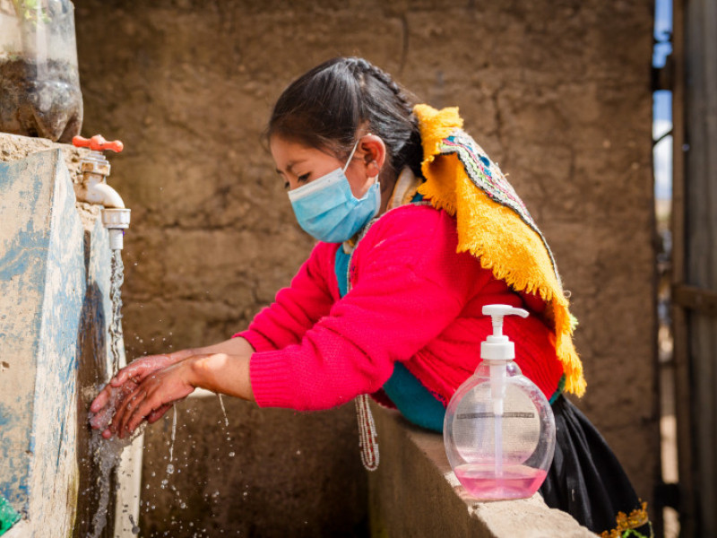 Luz Clarita washes her hands while wearing a mask at her home in Cuzco, Peru