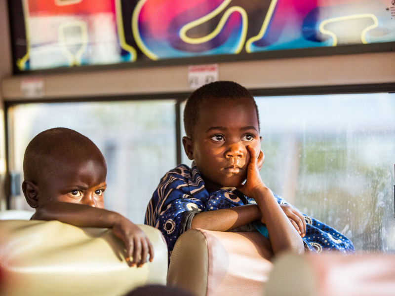 Burundian refugee children on board bus to transfer them to Nduta camp