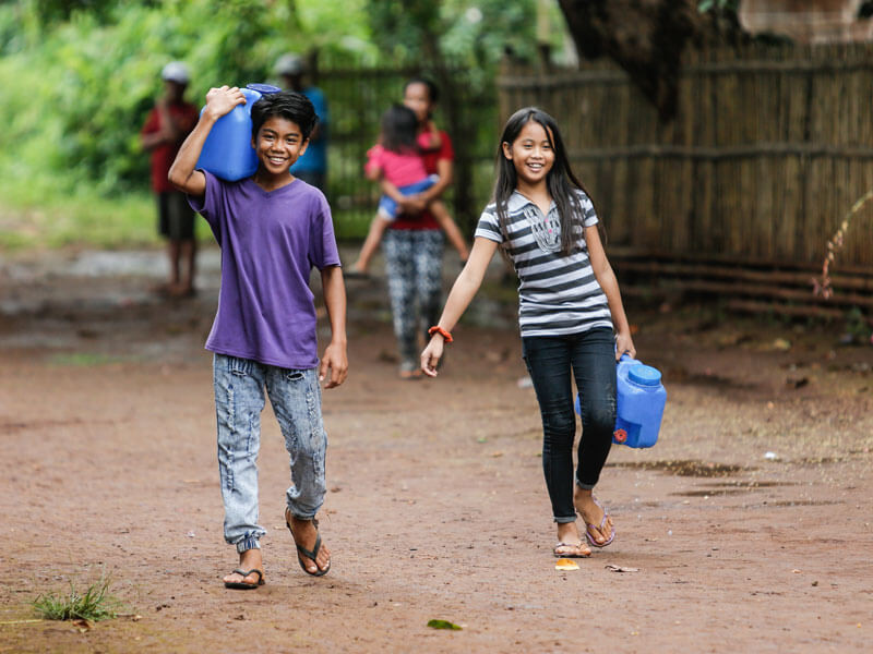 Danica-10-and-her-brother-Darwin-12-carry-home-water-from-the-new-pump.j